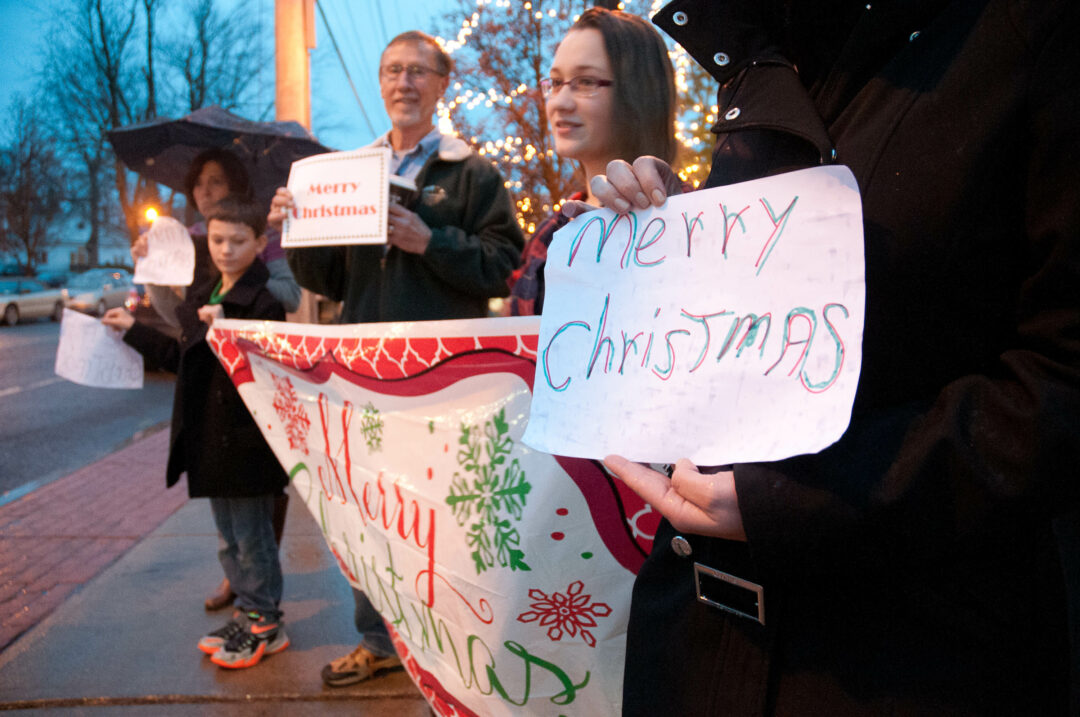 A small band of Bethlehem residents gather to protest the town's decision to reject a woman's request to post a Merry Christmas sign there. Photo by Michael Hallisey/Spotlight