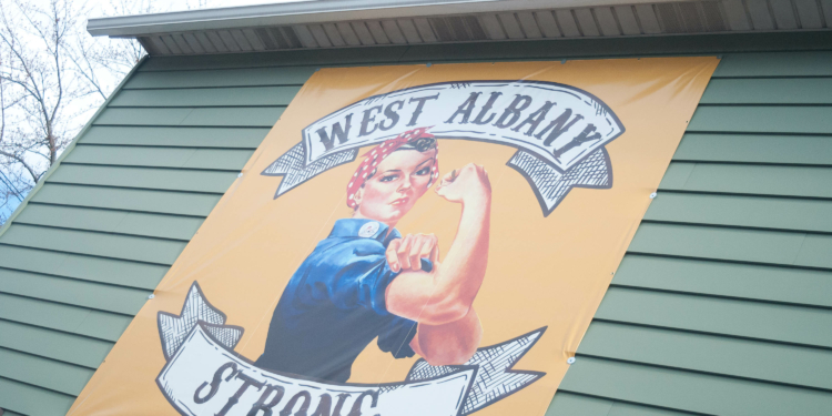 """A """"West Albany Strong' banner hangs off the side of Recycled Salon hair salon, where hair stylist Jacquelyn Porreca was murdered. For salon owner David Belschwinder, the banner defines the positive spirit of the neighborhood. Michael Hallisey/Spotlight"""