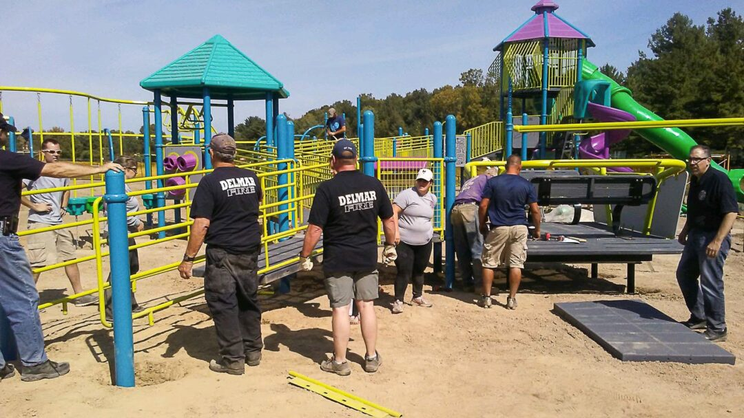 """BETHLEHEM —Volunteers showed up at Elm Avenue Park on Saturday, Sept. 17, to take part in a community build day helping to install brand new playground equipment funded by grant money that was secured by local Assemblymember Patricia Fahy (D-109).  In four two-hour shifts, approximately 100 volunteers, guided by a crew from Miracle Recreation, shoveled dirt, mixed and poured concrete, and helped assemble the new state-of-the-art playground. """"It was my honor to help mix and pour some concrete,"""" said Jesse Calhoun, the Republican candidate running against Fahy in the upcoming election. """"It was humbling to see all the firefighters out helping — they are the real heroes here, helping to make our communities better every day. They must help with tasks like this more often than we imagine. """"As a preschool teacher,"""" he said, """"I have to say that this seems to be one the most fun looking playgrounds around. The design team did a great job creating a playground that allows children to take risks and get some solid gross motor exercise. I just might have to take my preschool class on a field trip!"""" The equipment was purchased with part of a $250,000 state grant, the only money Bethlehem is currently set to receive of more than a billion dollars appropriated for the State and Municipal Facilities Program (SAM), a discretionary fund from which state legislators can request specific amounts for capital projects such as infrastructure maintenance and upgrades for municipalities within their districts. While critics say that discretionary funds, such as SAM, allow too much opportunity for corruption among those who control the flow of those funds—namely, legislative leadership and the governor—Assembly Speaker Carl Beastie defended the program earlier this year, saying the money was """"going to government entities to do good things,"""" and claiming that there is adequate oversight regarding its apportionment. The rest of the $250,000 secured by Fahy was spent on a new kayak launch at H"""