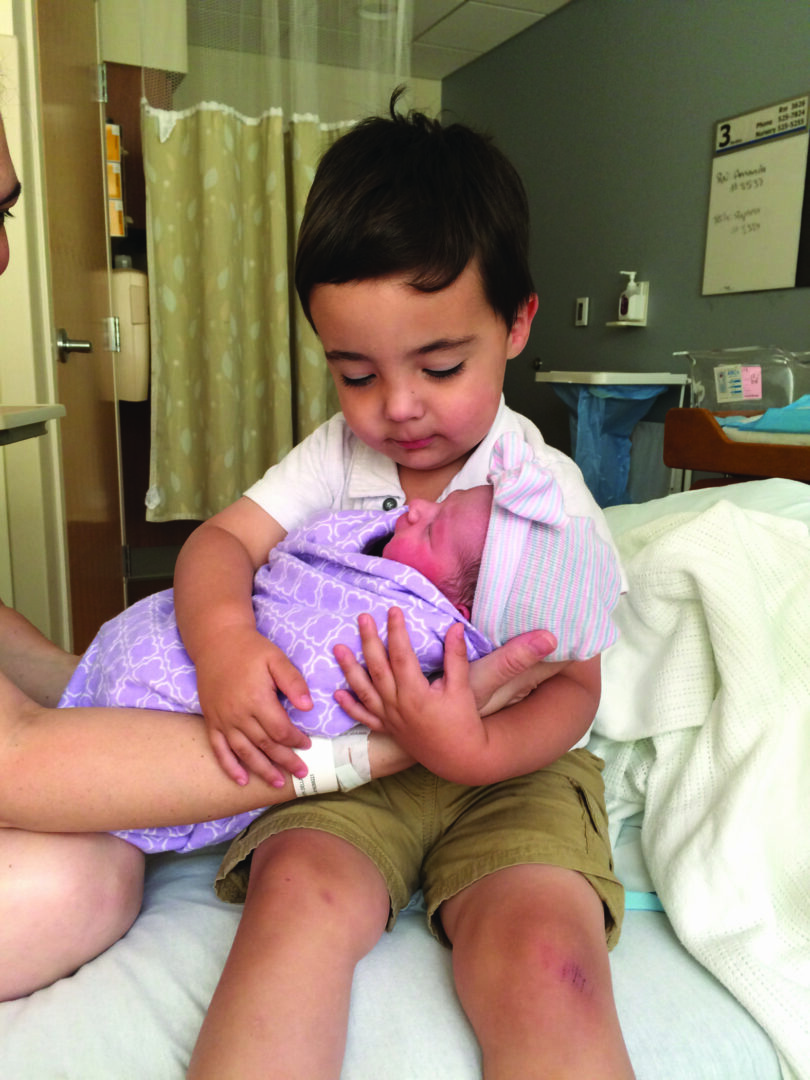 Jack holds his newborn baby sister, Cadence.