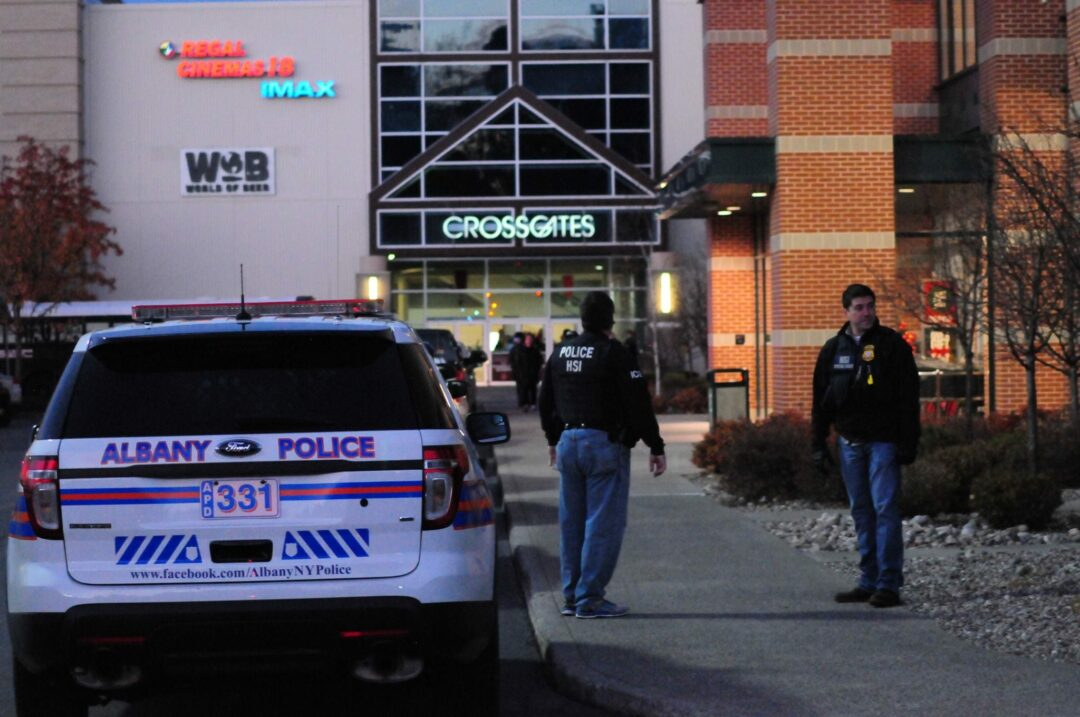 A pair of police officers stands outside the entrance to Dick's Sporting Goods at Crossgates Mall Saturday afternoon after an alleged shooting took place.