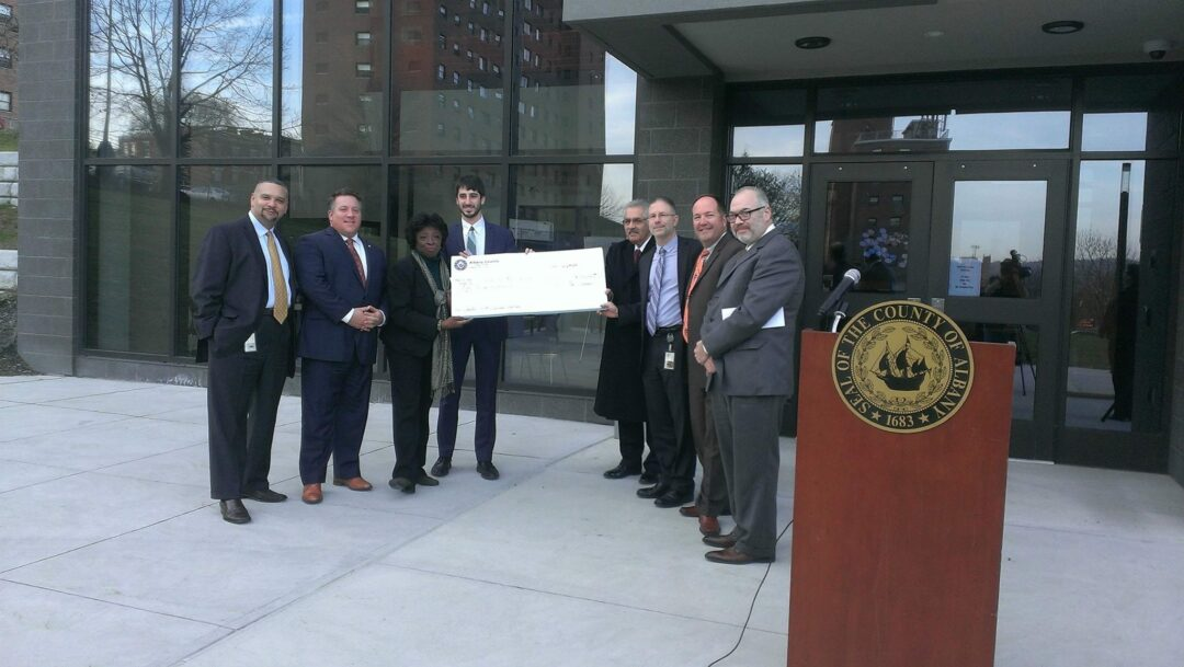 """McKnight, Fein and Commisso hold the over-sized, overdue $50,000 check presented to Trinity Alliance officials at Dec. 10 press conference where McCoy announced that the funds had been """"allocated."""" // Photo: County Executive, Facebook page"""