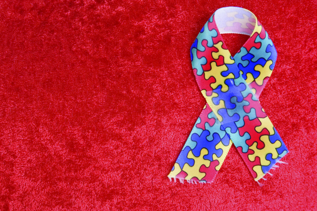 Autism ribbon on textured red background