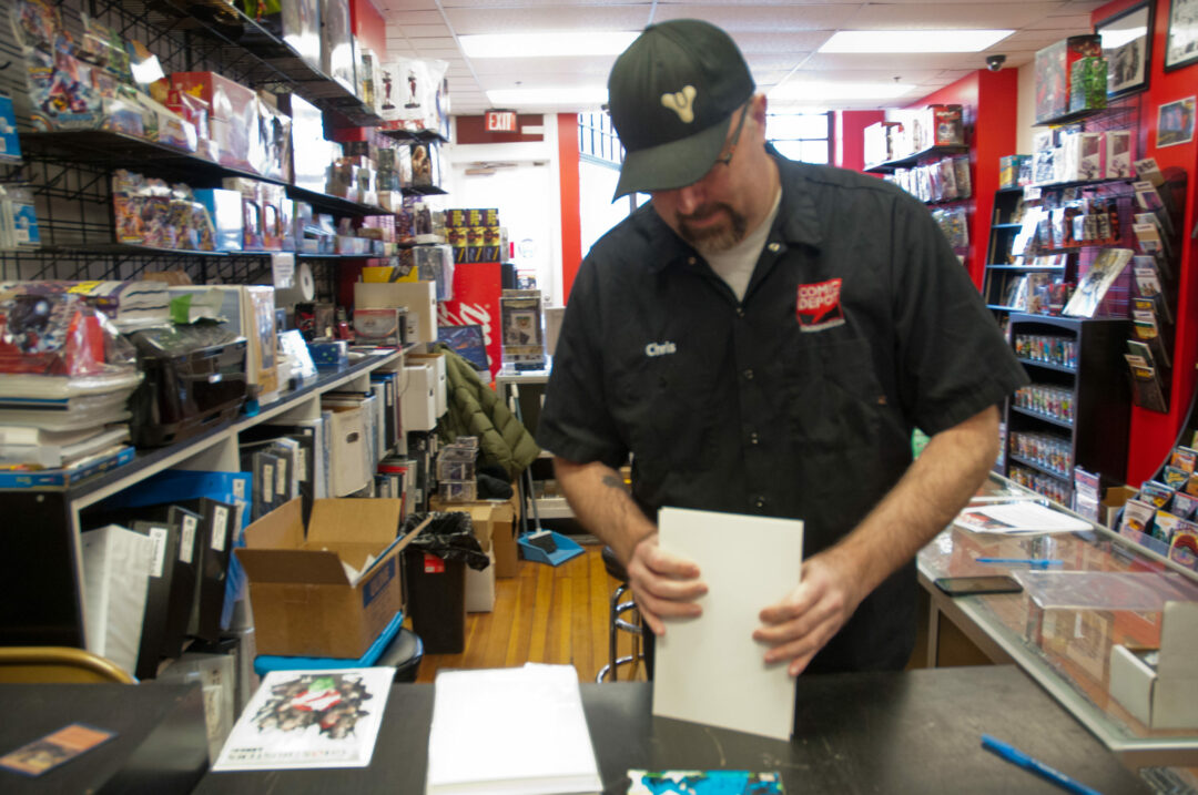 Chris Kaminski works behind the counter of The Comic Depot  in Saratoga Springs,  where a special auction is taking place to help  his late friend,  Darren Carrara. (Michael Hallisey / The Spot518)