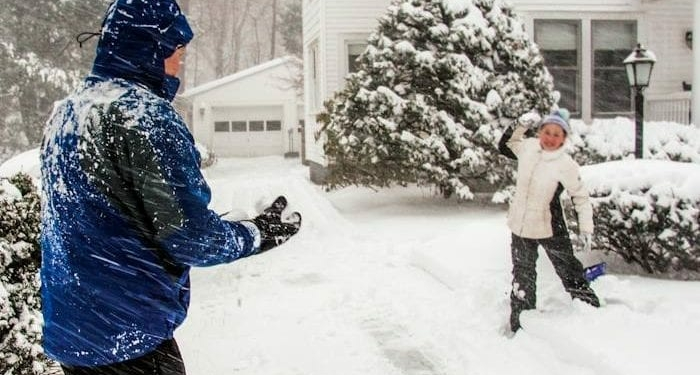 A father and daughter take a moment to play in the snow after shoveling off their driveway in Elsmere, Tuesday, March 14. Photo by Michael Hallisey / SpotlightNews