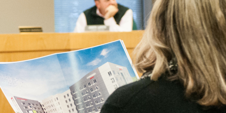 One resident looks over a proposed plan at a recent Colonie Planning Board meeting. Despite grumbling over development and traffic congestion, nearly everyone polled by Siena College this year loves living here. (Photo by Jim Franco / Spotlight News)
