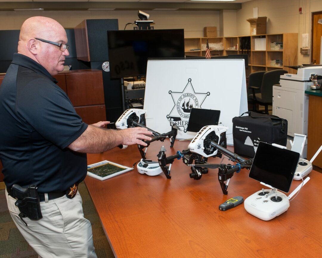 ommander Lee Bormann in front of the Sheriff Department's new drones. Photo by Jim Franco / Spotlight News