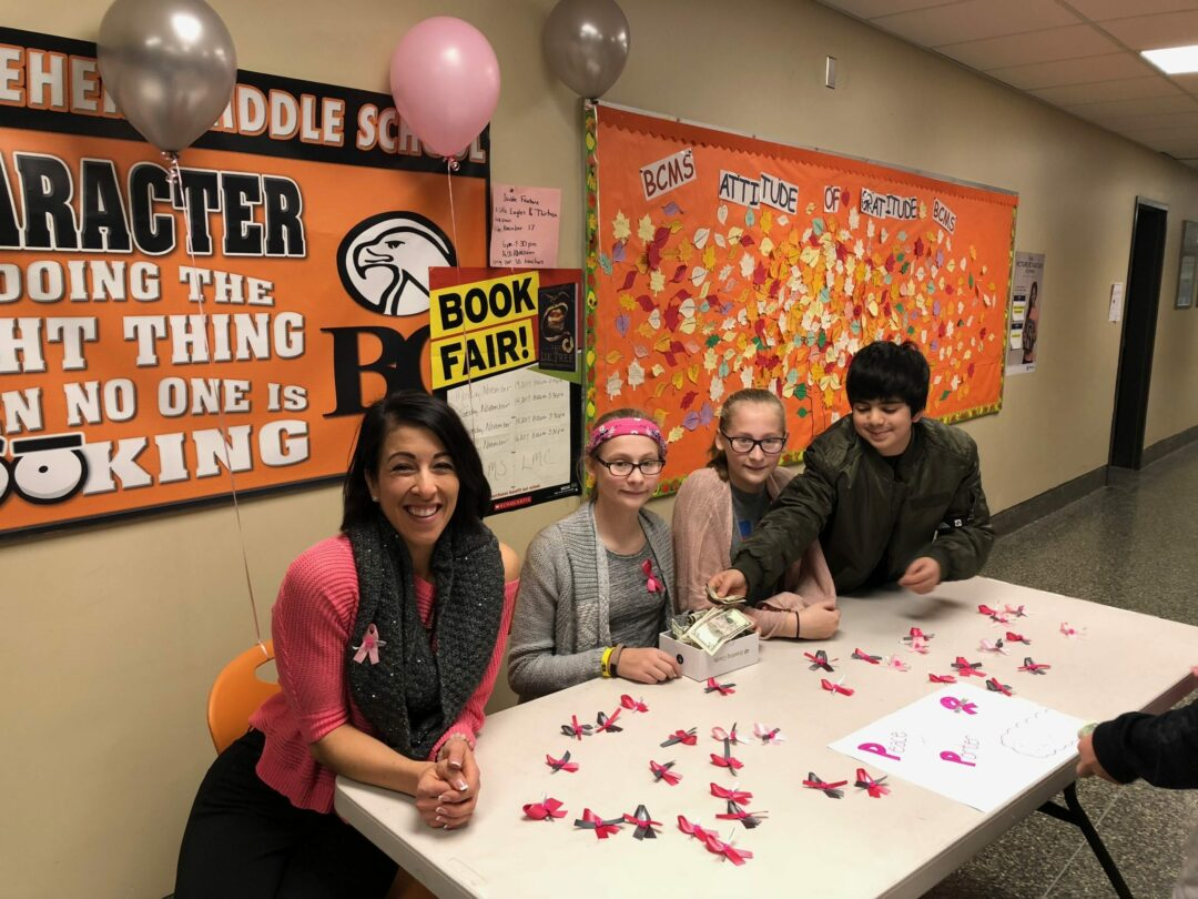 Marcucci and students Emma and Juliette VanLuven, joined by Albi Snyder, sell pink and gray ribbons in memory of Porter.  Submitted photo