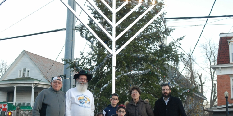 (L. to R.  Haim Ben-Eliezer, Rabbi Nachman Simon, Rochel Leah, (in back) Menachem Simon, Mendel Simon, Clara Simon, Rabbi Zalman Simon, Moussia Simon) (photo by Ali Hibbs/Spotlight News)