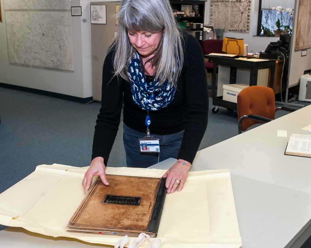 Jill Hughes, the Albany County archives clerk, at the Hall of Records, with a book of interments. (Photo by Jim Franco/Spotlight News)