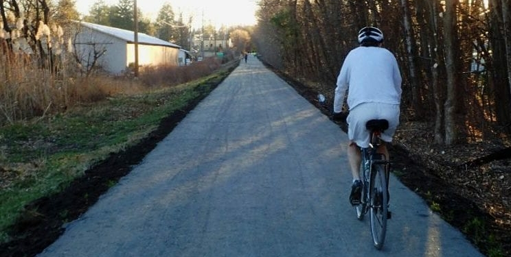 A bicyclist on the Albany County Helderberg Hudson Rail Trail approches Delmar's Warehouse District on an autumn day. Local businesses are seeing more people visit them by means of the Rail Trail, and could see more in the coming weeks.  Spotlight file photo