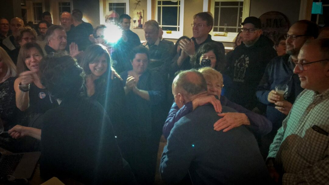 Winner Dan Coffey, above, receives a congratulatory hug and is surrounded by supportive colleagues, friends and fellow Democrats. Michael Hallisey / Spotlight News