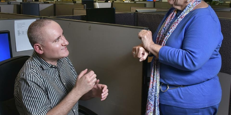 Tobi Bickweat, right, signs with an employee. More than half of eBizDocs employees are disabled.  eBizDocs