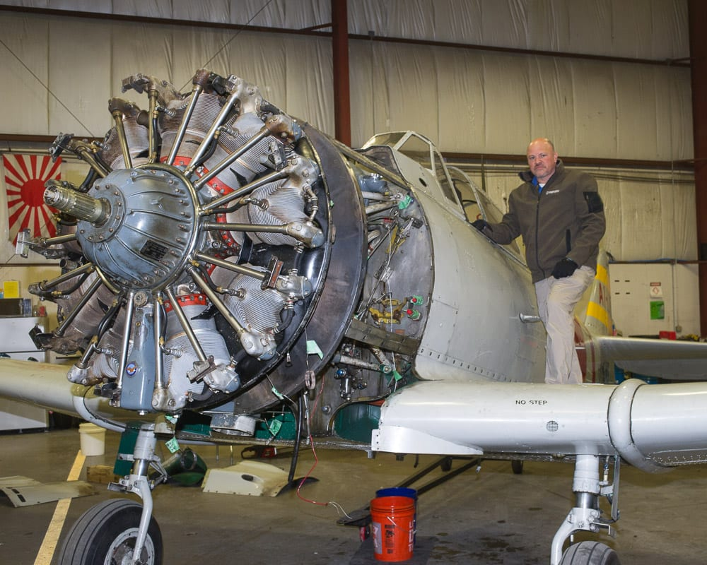 Integra Optics CEO David Prescott stands on the wing of a Japanese Zero replica in his hangar at the Albany International Airport.