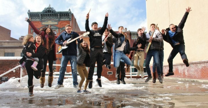 """Troy Music Academy students and instructors jumping outdoors along the rooftop area of the Troy Atrium after performing as part of """"The Beatles"""" Rooftop concert held in Troy, NY, Wednesday, January 30,2019. Photo Credit: Amy Modesti"""