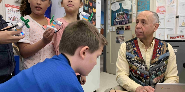 Dr. Alan Fiero, right, tasked his second graders to build a cooling fan from LEGO pieces, connect them wirelessly to their Chromebooks, and program them to perform tasks. Diego Cagara / Spotlight News