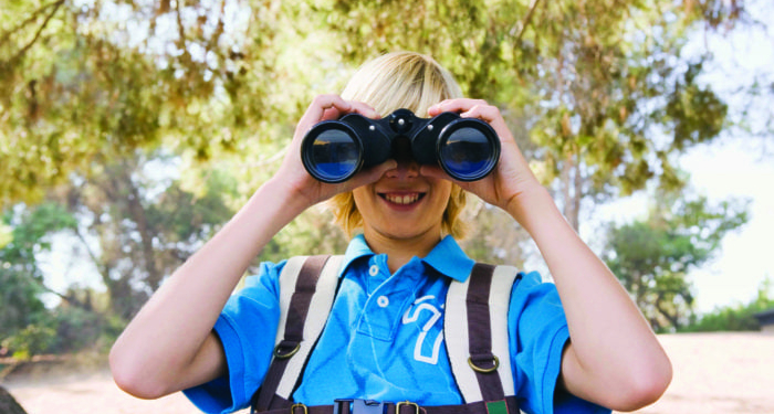 Boy with binoculars and backpack