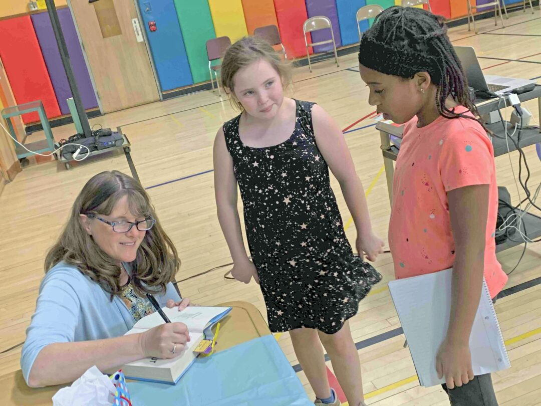 Children's author Kate Messner, left, signs a book and has said that children have sometimes given her ideas for her books. Diego Cagara / Spotlight News