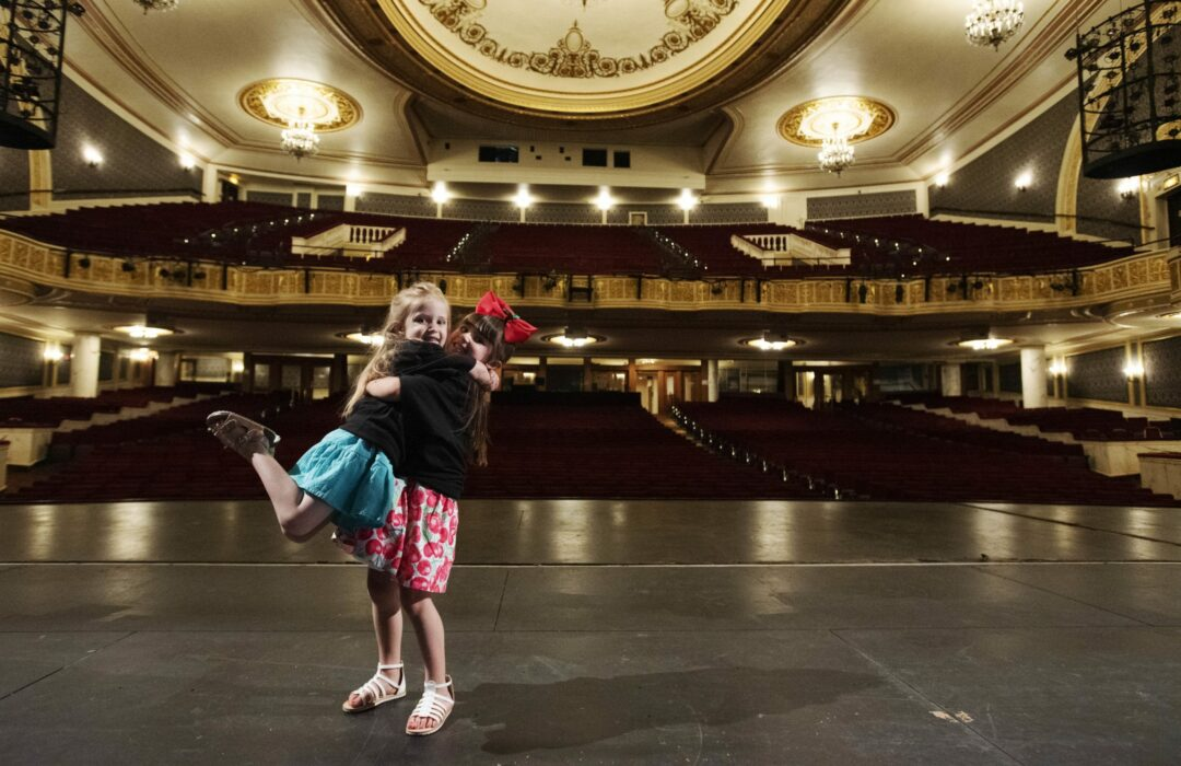 Viviana DiMezza, 5, of Perth, right, lifts Genevieve Carmichael, 4,  of Amsterdam, on the Proctors stage after the announcement the two will share the role of Lulu in Waitress at Proctors Friday, May 31, 2019. The girls were selected out of about 40 local 4 and 5-year-olds who auditioned for a national casting director at Proctors for the role of Lulu, the daughter of the lead character in Waitress. Waitress is at Proctors June 11-16.