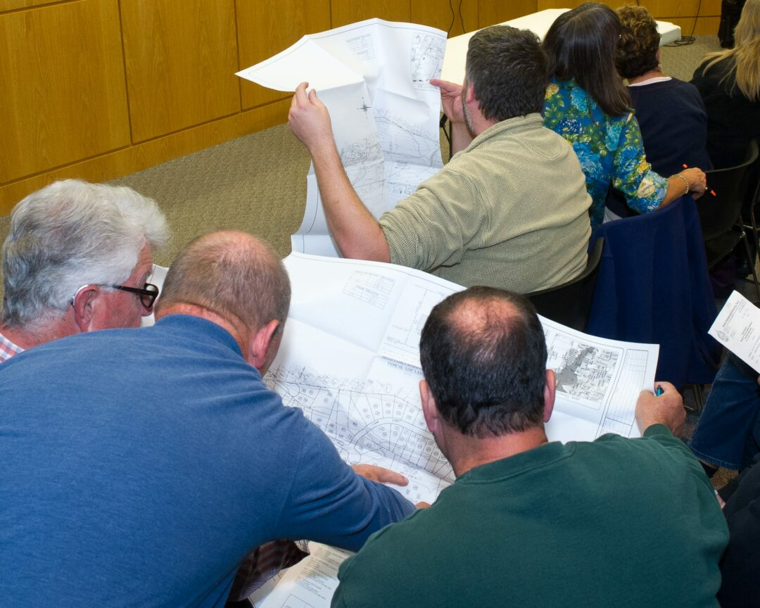 Residents look at blueprints of a project during a Colonie Planning Board meeting.  Jim Franco/Spotlight News