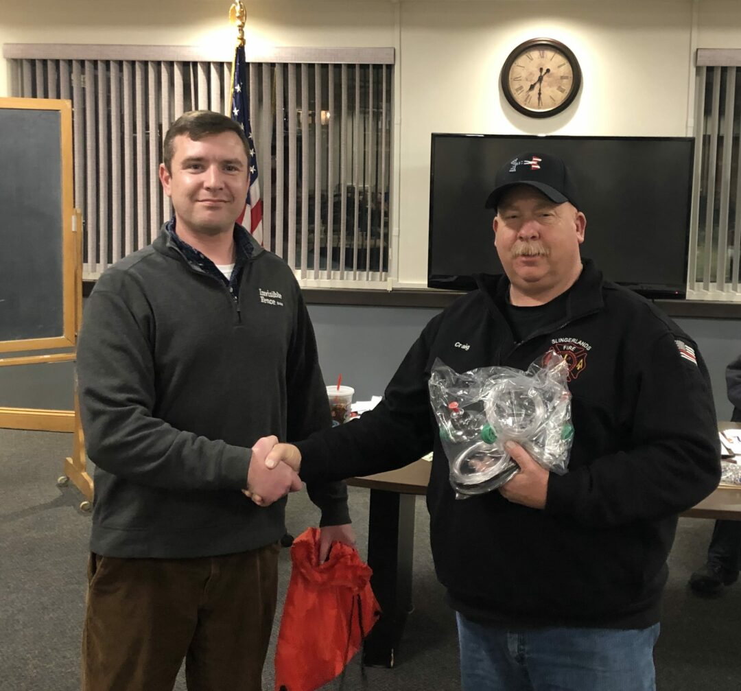 Invisible Fence representative Mark Lundgren, left, visited the Slingerlands Fire Department to donate the pet oxygen masks, which Chief Craig Sleurs, right, received on behalf of his colleagues. Provided photo