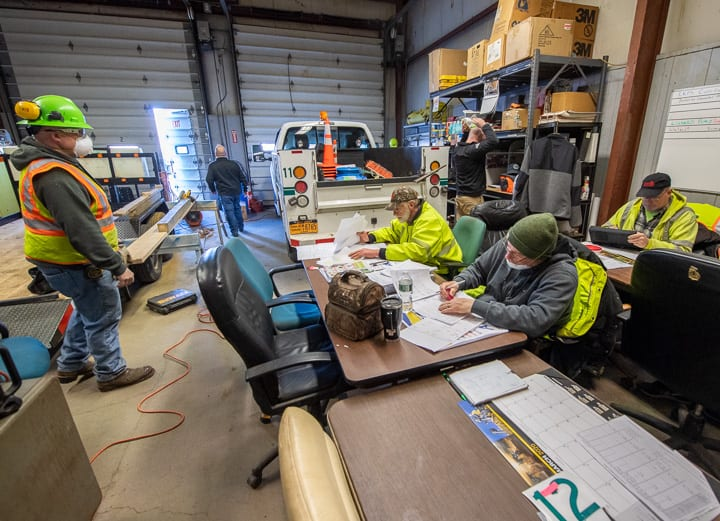 Workers at the Division of Pure Waters Collection Section squeeze by a utility truck to do paperwork while another worker was cutting wood to fix a trailer.    Jim Franco / Spotlight News