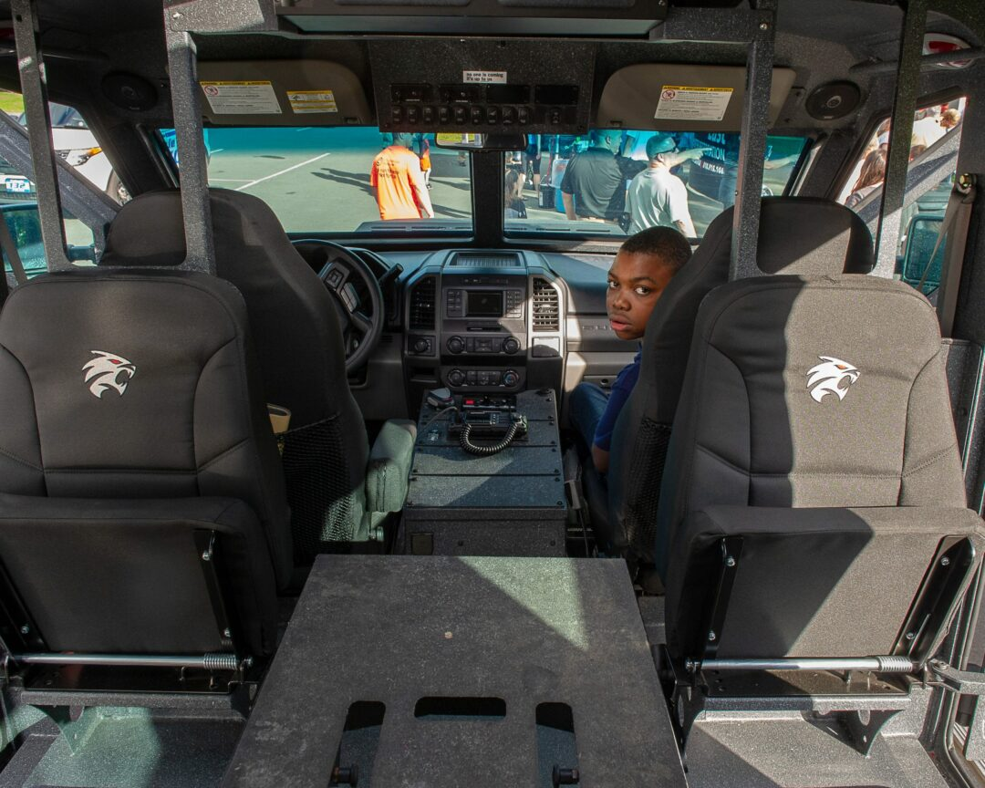 A young town resident sits in the armored vehicle during a community day at the Crossings in 2019.    Jim Franco/Spotlight News