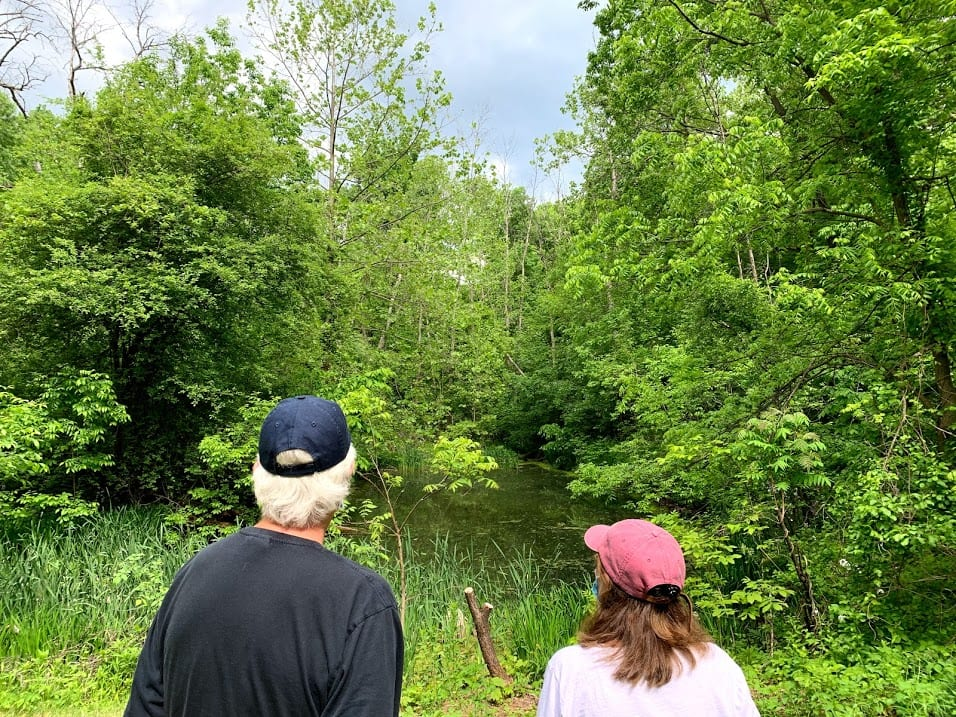 Residents look out to the pond at the Hollyhock Hollow Sanctuary, a new preserve that offers a natural respite from the outside world. Diego Cagara / Spotlight News