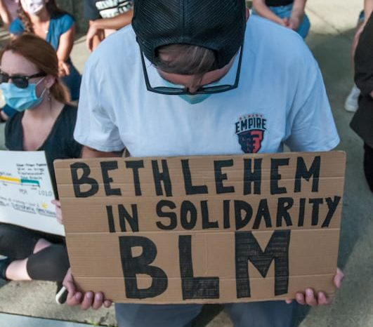 A Black Lives Matter demonstrator kneels at a June rally held at Delmar's Four Corners. Town Board members have voiced support for the movement in recent months. Michael Hallisey / Spotlight News