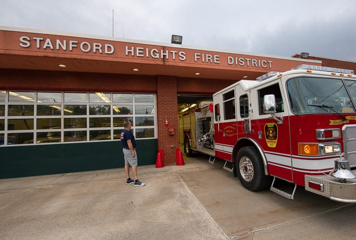 Second Assistant Chief Patrick Boccio demonstrates how tight of a squeeze it is to get trucks in and out of Stanford Heights Fire Department while Chairman of the Board of Commissioner Kevin Hulett watches.   Jim Franco/Spotlight News