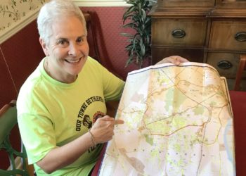 Jane Sanders holds a map of her hometown of Bethlehem. Each streak of fluorescent yellow is a street she visited on her bicycle. Photo submitted