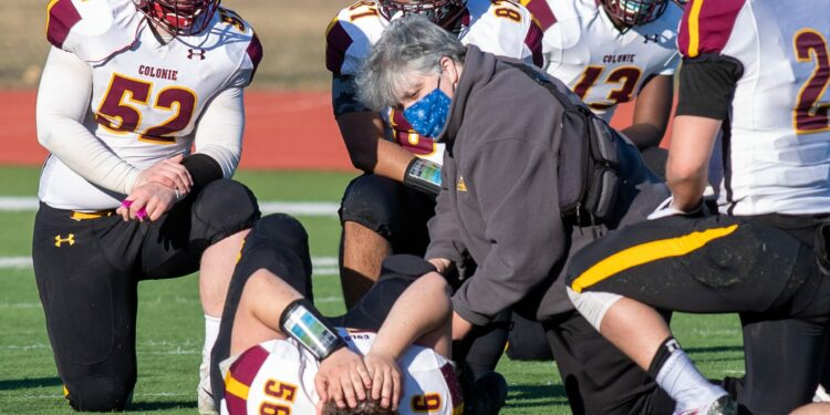 Colonie High School Athletic Trainer Aimee Brunelle tends to an injured football player during a game against Schenectady. (Jim Franco / Spotlight News)