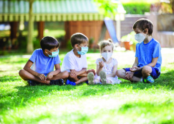 Young children in protective masks on faces outdoors. Quarantine. Kids wearing safety masks while sitting on grass in park. Coronavirus prevention.