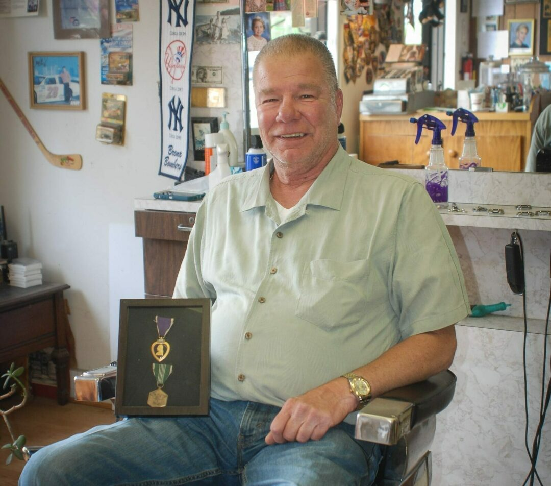 Delmar Barber Joe Bruno sits in his barber's chair on Delaware ave with his Purple Heart.