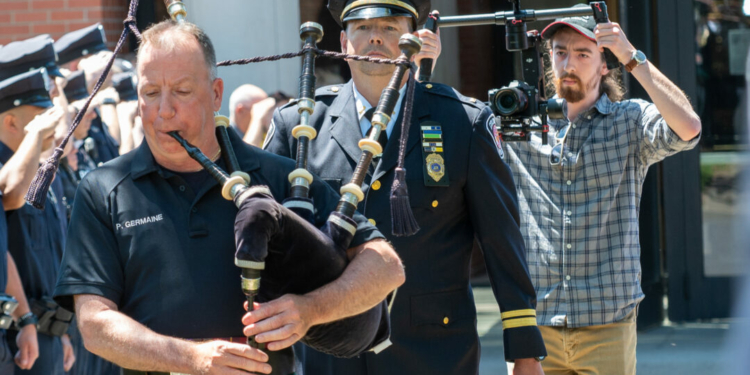 A member of the Elevation 10 K film crew records the walking out ceremony for retiring Lt. Robert Barrett. Jim Franco/Spotlight News