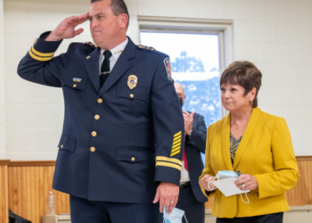 Colonie Police Chief Mike Woods salutes a room full of police officers after being sworn in by Supervisor Paula Mahan (Jim Franco /Spotlight News)