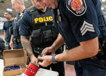 Colonie Sgt. Derek Breslin inspects a weapon turned in for cash at a gun buyback program in Watervliet on Saturday, Oct. 9.  Jim Franco / Spotlight News.